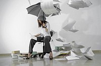 Woman sits indoors under an umbrella, paperwork falling from above.