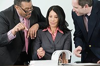 Two businessmen and a businesswoman discussing in an office