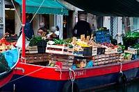 Close up of fruit and vegetable market on colourful blue and red barge with motion blur of vendor and shoppers, sunny autumn morning in Venice, Northe...
