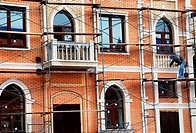 construction of house with arch window and balcony