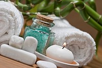 An spa background with bath salts, a towel and a candle.