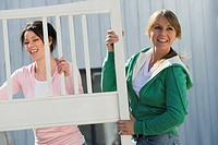 Women carrying bed frame