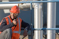Engineer talking on a walkie_talkie at a plant