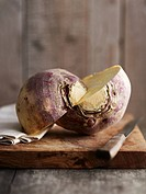 A turnip, halved, on a chopping board