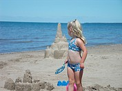 A young blond girl looks over her shoulder at the water with a toy in hand at the beach