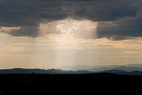 Shaft of sunlight through rainclouds in Santa Fe, New Mexico. Jemez Mountains in the background. Wide angle lens