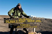 Trekking, mountain climber standing at the sign at the summit of Gilman's Point, stepped glacier on the crater rim, Kilimanjaro, Marangu Route, Tanzan...