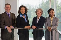 Business executives leaning against a railing