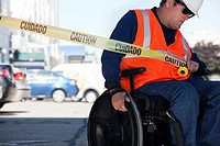 Facilities engineer in a wheelchair pulling caution tape across road