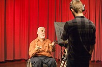 Man with muscular dystrophy and diabetes speaking on a camera in a TV studio