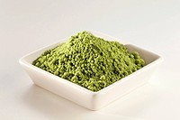Japanese Matcha Green Tea Powder in a White Dish, White Background
