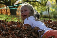 girl playing in leaves in fall