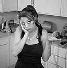 Unhappy weeping woman with hand on face in a kitchen