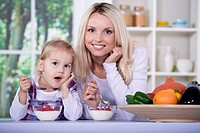 a young woman and little girl eating yogurt in the kitchen