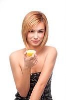 portrait of a young, blonde woman, holding half a lemon in one hand and havind a sour taste expression on her face.