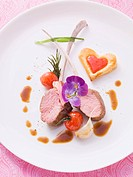 Medium rare lamb chops with heart_shaped puff pastries