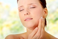 Woman applying moisturizer cream on face. Close_up fresh woman face.