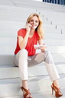 Blond woman having a snack on stairs