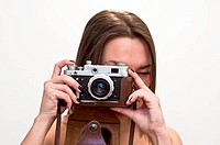 Young woman looks at an old film camera. Studio shot on white background.