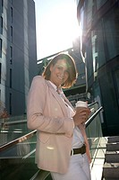 Smiling businesswoman with coffee to go outdoors