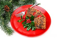 Delicious holiday fruitcake on a red plate garnished with holly. White background with pine branches.