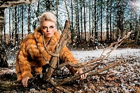Woman wearing a fur coat in the forest.