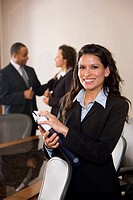 Hispanic businesswoman standing in boardroom, colleagues in background