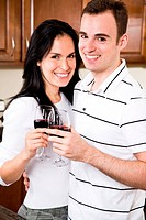 A beautiful interracial couple toasting wine in the kitchen