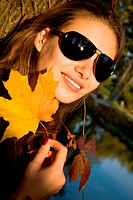 Beautiful girl smiling at the background of the autumn woods