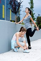 Female athletes taking a rest, one doing stretching