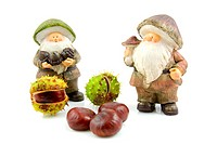 stone autumn statue doll of gnome with chestnuts isolated on white background