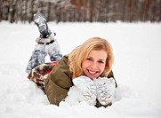 a beautiful woman is lying at the snow in the park
