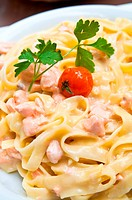 close_up of plate of pasta and smoked salmon with tomato