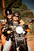Man and Woman riding on vintage motorcyle