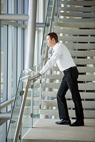 Businessman stands on an office stairway.