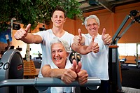 Successful fitness team in a gym holding thumbs up
