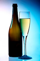 bottle and glass of champagne with ambient cool blue with a hint of pink backlighting