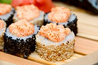 Close_up of of sushi on wood plate.