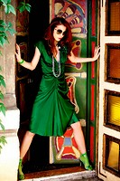 red hair woman in elegant green dress in doorway, outdoor shot
