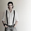 Portrait of an attractive relaxed male model in white shirt, suspenders, and jeans with his hands in pockets
