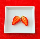 Two halves of strawberry, over a white plate, over a red cloth