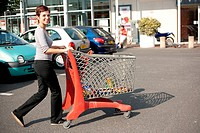 woman driving shopping cart on supermarket car park