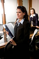 Young Hispanic businesswoman in boardroom with colleague in background