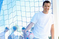 Man stands at a soccer goal while holding a soccer ball.