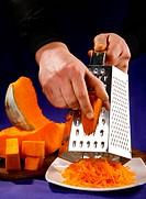 Preparing orange pumpkin with grater on blue