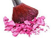 Makeup brush with purple crushed eye shadow, isolated on white macro