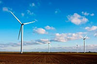 Modern energy generators, wind turbines in a field. Blue sky with clouds