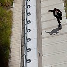 Businessman rides a skateboard up a concrete slope.