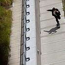 Businessman rides a skateboard up a concrete slope.
