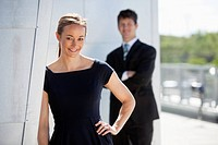 Businesswoman smiles outdoor while a colleague stands in the background.